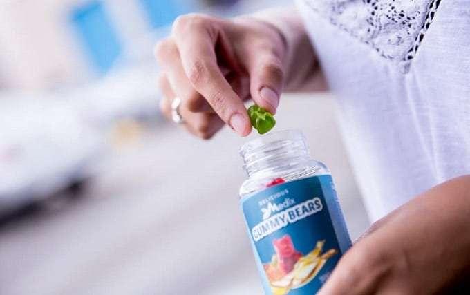 Holding Bottle Of CBD Gummies